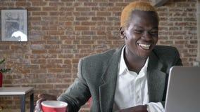 Hombre de negocios africano acertado joven que mecanografía en el ordenador portátil y que anima, ganador feliz que sonríe en ofi metrajes
