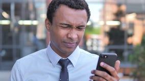 Hombre de negocios africano al aire libre trastornado por la pérdida mientras que usa smartphone metrajes