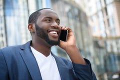 Hombre de negocios africano alegre usando el teléfono para la comunicación Imágenes de archivo libres de regalías