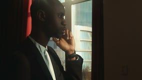 Hombre de negocios africano, americano que habla en el teléfono almacen de video