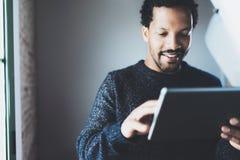 Hombre de negocios africano barbudo atractivo usando la tableta mientras que se coloca en su Ministerio del Interior moderno Conc Imagen de archivo libre de regalías
