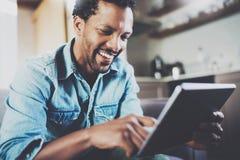 Hombre de negocios africano barbudo atractivo usando la tableta mientras que se sienta en el sofá en su hogar moderno Concepto de Imágenes de archivo libres de regalías