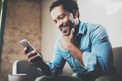 Hombre de negocios africano barbudo feliz usando el teléfono mientras que se sienta en el sofá en su hogar moderno Concepto de tr Fotos de archivo libres de regalías