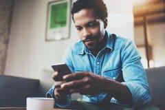 Hombre de negocios africano barbudo pensativo usando el teléfono mientras que se sienta en el sofá en su hogar moderno Concepto d Fotos de archivo