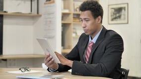 Hombre de negocios africano Browsing en la tableta metrajes