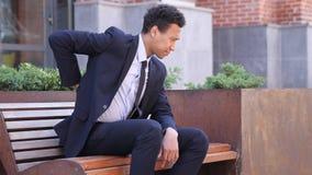 Hombre de negocios africano cansado Relaxing Back Pain, oficina exterior foto de archivo