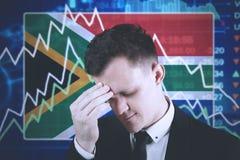 Hombre de negocios africano con el gráfico decreciente de las finanzas Foto de archivo