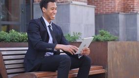 Hombre de negocios africano emocionado Celebrating Success en la tableta que se sienta en banco metrajes
