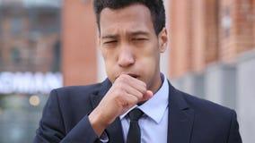 Hombre de negocios africano enfermo Coughing mientras que se coloca al aire libre foto de archivo