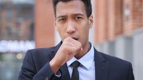 Hombre de negocios africano enfermo Coughing mientras que se coloca al aire libre almacen de video