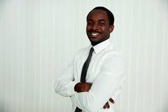Hombre de negocios africano feliz con los brazos doblados Imagen de archivo libre de regalías