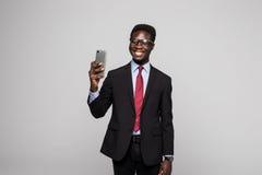 Hombre de negocios africano feliz joven que toma el selfie en fondo gris foto de archivo