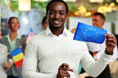 Hombre de negocios africano feliz que sostiene la bandera de los E.E.U.U. Fotografía de archivo