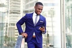 Hombre de negocios africano joven usando el teléfono móvil Imagenes de archivo
