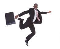 Hombre de negocios africano que corre sosteniendo la cartera Fotos de archivo
