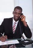 Hombre de negocios africano que habla en el teléfono imagen de archivo