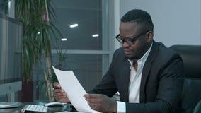 Hombre de negocios africano que hace el papeleo, proyectos de ley de finanzas calculadores en oficina