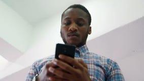Hombre de negocios africano que lleva a cabo la situación disponible del teléfono en oficina moderna almacen de metraje de vídeo