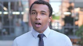Hombre de negocios africano que se pregunta chocado, al aire libre almacen de video