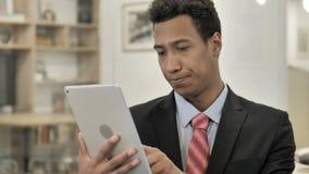 Hombre de negocios africano que usa la tableta almacen de metraje de vídeo