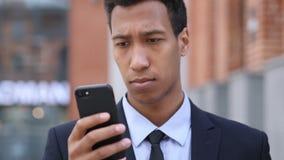 Hombre de negocios africano Using Smartphone para hojear en línea metrajes