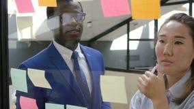 Hombre de negocios africano y empresaria asiática que investigan notas pegajosas sobre el vidrio almacen de video