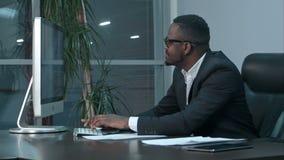 Hombre de negocios afroamericano acertado que se sienta en el escritorio, trabajando en el ordenador portátil genérico, mecanogra almacen de metraje de vídeo