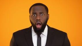 Hombre de negocios afroamericano aterrorizado que mira a la cámara, evasión fiscal, sorpresa metrajes