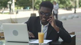 Hombre de negocios afroamericano atractivo joven con los vidrios y el ordenador portátil que se sientan en barra del café y que h almacen de metraje de vídeo
