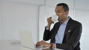 Hombre de negocios afroamericano casual Drinking Coffee mientras que trabaja en el ordenador portátil almacen de video