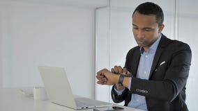 Hombre de negocios afroamericano casual Using Smartwatch para comprobar notificaciones almacen de video