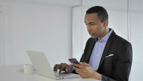 Hombre de negocios afroamericano casual Working en Smartphone y ordenador portátil en oficina almacen de video