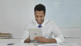Hombre de negocios afroamericano Celebrating Success del proyecto sobre la tableta almacen de video