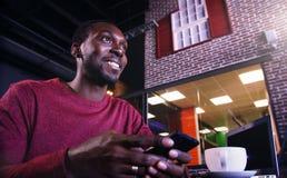 Hombre de negocios afroamericano con el ordenador portátil en un café Fotografía de archivo