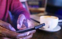Hombre de negocios afroamericano con el ordenador portátil en un café Foto de archivo