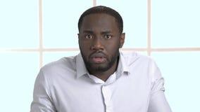 Hombre de negocios afroamericano confuso en la camisa blanca