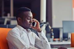 Hombre de negocios afroamericano en el teléfono que se sienta en el ordenador en su oficina imagen de archivo