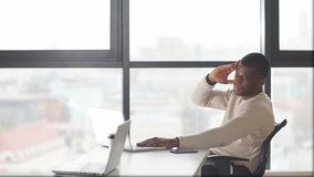 Hombre de negocios afroamericano en un funcionamiento del traje de negocios en el ordenador portátil almacen de video