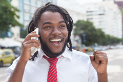 Hombre de negocios afroamericano feliz con los dreadlocks en el teléfono Foto de archivo libre de regalías
