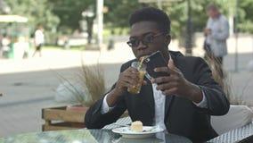 Hombre de negocios afroamericano feliz que toma el selfie en café almacen de metraje de vídeo