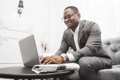 Hombre de negocios afroamericano joven en un traje gris que trabaja detr?s de un ordenador port?til foto de archivo