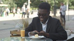 Hombre de negocios afroamericano joven hermoso usando el teléfono elegante, mensajería su novia, comiendo en el café Fotos de archivo libres de regalías