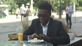 Hombre de negocios afroamericano joven hermoso usando el tel?fono elegante, mensajer?a su novia, comiendo en el caf? metrajes
