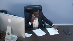 Hombre de negocios afroamericano joven pensativo que tiene una llamada de teléfono, discutiendo documentos y sentándose en oficin almacen de metraje de vídeo