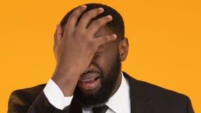 Hombre de negocios afroamericano joven que hace el gesto de la palma de la cara, plazo vencido metrajes