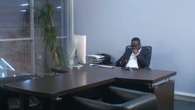 Hombre de negocios afroamericano joven que hojea con el smartphone, sentándose en oficina metrajes