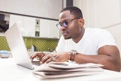 Hombre de negocios afroamericano joven que trabaja en un ordenador port?til en la cocina en un interior moderno imagen de archivo