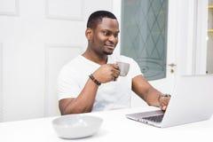 Hombre de negocios afroamericano joven que trabaja en un ordenador port?til en la cocina en un interior moderno foto de archivo libre de regalías
