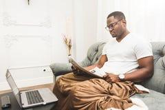 Hombre de negocios afroamericano joven que trabaja remotamente en casa en un ordenador port?til fotos de archivo libres de regalías