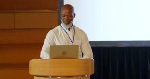 Hombre de negocios afroamericano mayor que habla en etapa en el podio en el auditorio 4k metrajes